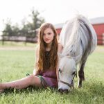 teen girl sitting on grass while grey pony grazes