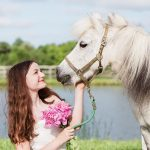 teen girl sitting on grass looking at min horse