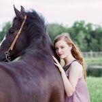 teen girl pressed up against bay horse