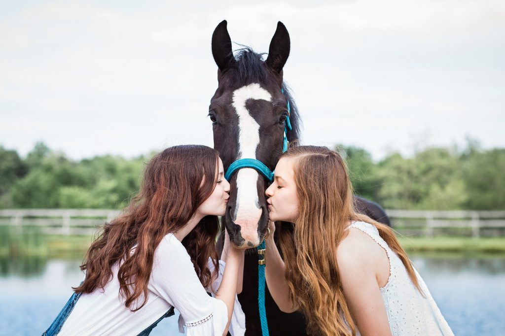 two teen girls kissing each side of horse's muzzle