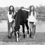 black and white image of two teen girls posed with grazing horse