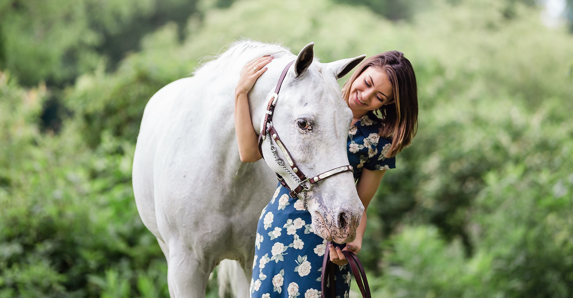 young woman with arm around horse's neck while making eye contact